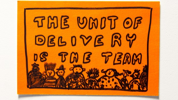 "Post-it note with a drawing of people and text that reads ""The unit of delivery is the team"""