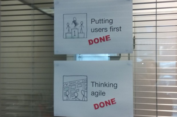 "Two A4 papers hanging on the window with drawings and text that reads ""Putting users first"" and ""Thinking agile"". Both sheets of paper are stamped as ""Done"""