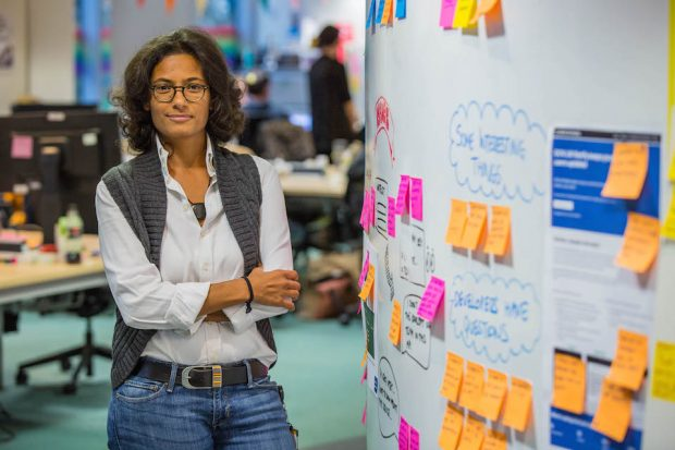 Fajer Qasem, Product manager, standing in an office next to the colourful post-it note wall