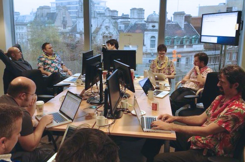 Colleagues in the office environment at GDS in 2012, sitting around the square table, next to computer screens and on laptops.