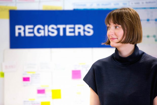 """Michaela standing in front of a camera next to a sign that reads """"Registers"""""""