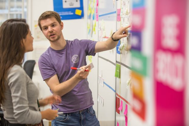 Thomas Fast Streamer, talking to a colleague next to a post-it notes wall