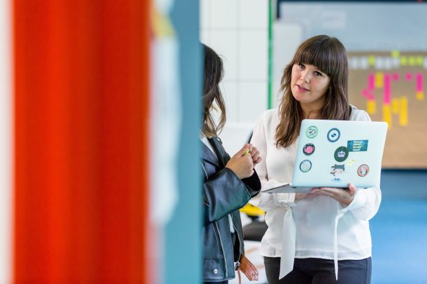 Amy Fox, talking with a colleague and holding a laptop in her hand