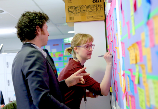 Colleagues are writing on the post-it wall