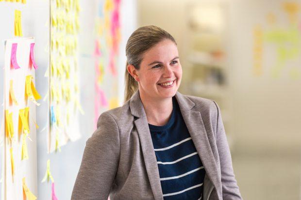Abi Giles-Haigh, Senior Data Scientist, next to a post-it wall