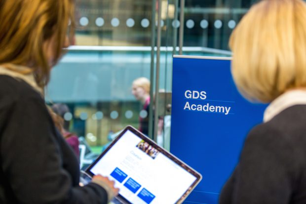 GDS Academy poster and two colleagues chatting next to it