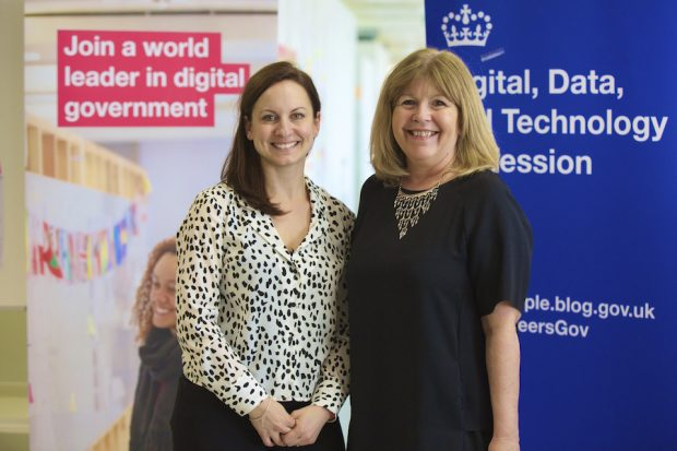 "Holly Ellis and Maggie Philbin with banners in the background that read ""Join a world leader in digital government"" and ""Digital, data and Technology Profession"""