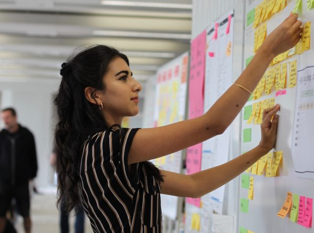 An intern attaching the post-it note on the board