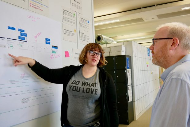 Liz Lutgendorff talking to a colleague next to a project board