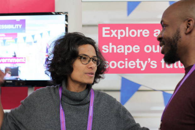 """An image of two colleagues talking. There's a banner behind reading """"Explore and shape our society's future"""""""