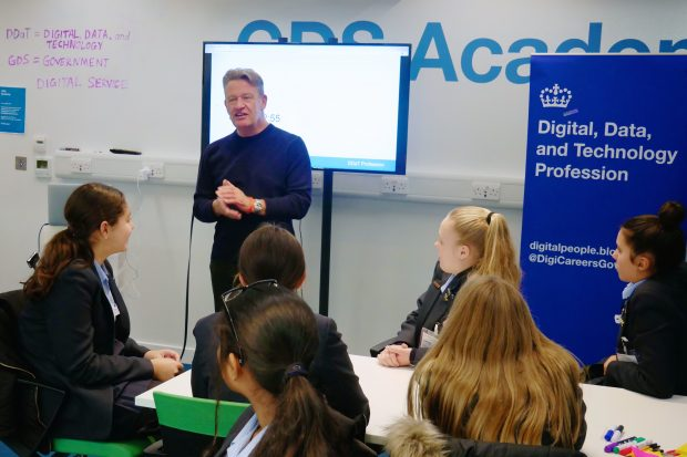 Kevin Cunnington, Director General of GDS and Head of the DDaT Profession, talks to a group of female students