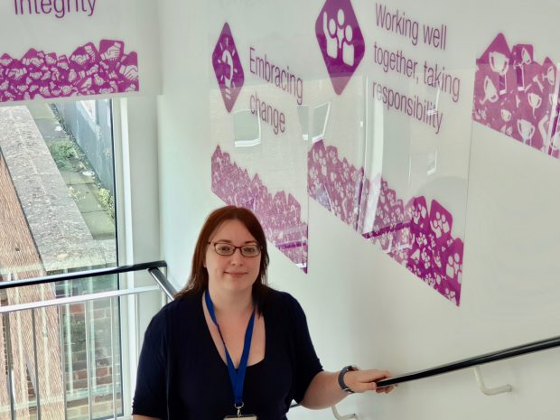 "Blog post author standing in the staircase, facing the camera. The walls have purple writings on them with sayings ""Working well together, taking responsibility"" and ""Embracing change"""