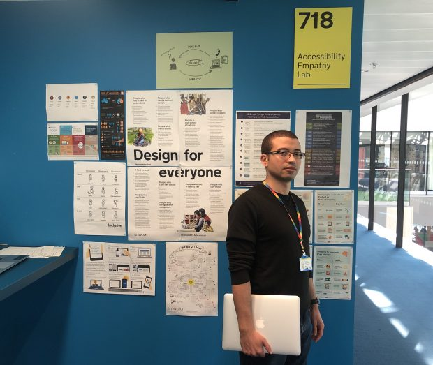 "Jonathan Glassman stands in front of a wall covered with posters. One of these reads ""Design for everyone""."