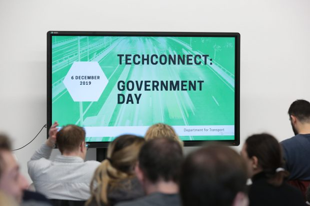 "A screen that reads ""6 December 2019. TechConnect: Government Day. Department for Transport."""